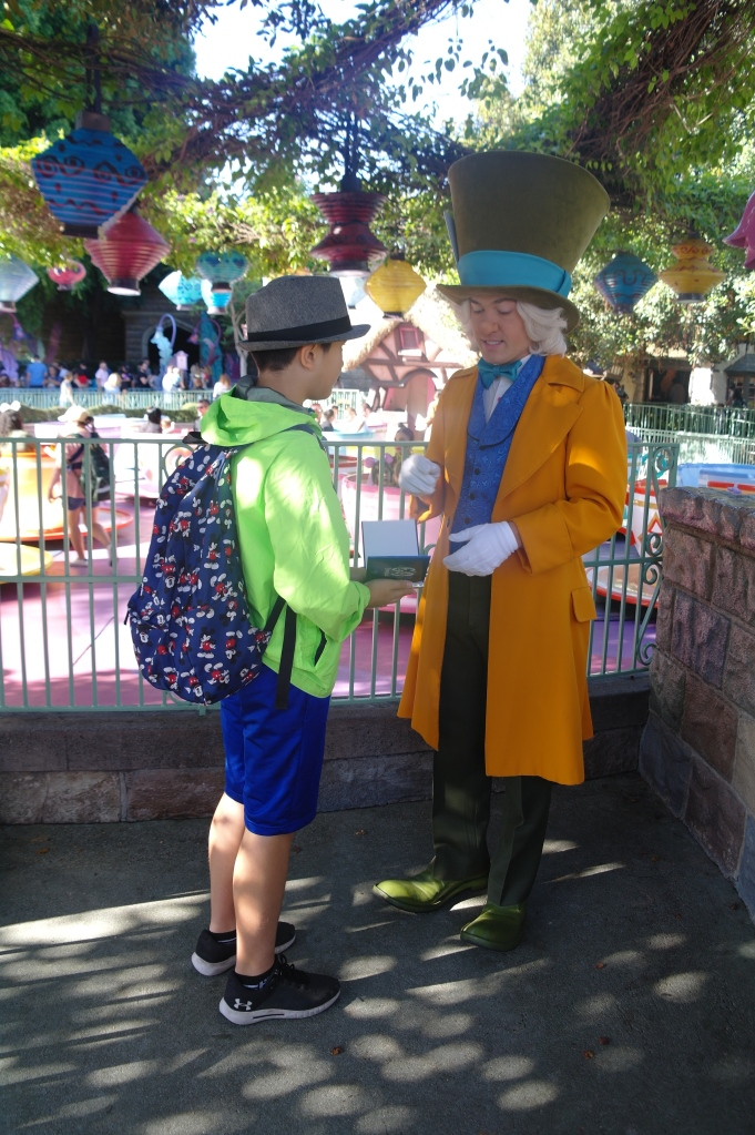 Boy getting autograph of Mad Hatter in Disneyland