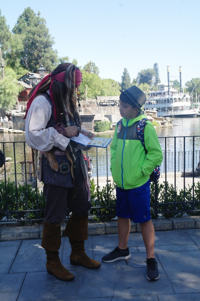 Boy getting the autograph of Jack Sparrow in Disneyland