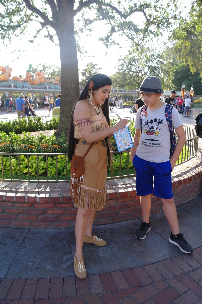 Boy getting the autograph of Pocahontas in Disneyland