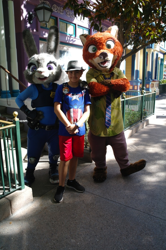 Boy meeting and taking a photo with Nike Wilde and Judy Hopps from Zootopia while in Disneyland
