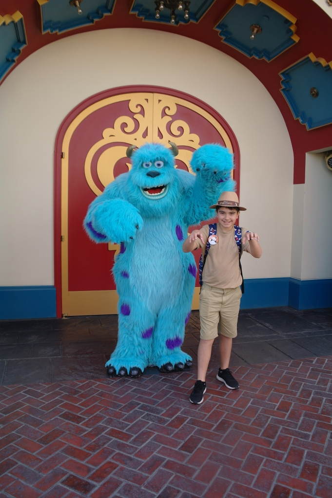 Boy showing his scary side with Sulley from Monster's Inc in Disneyland