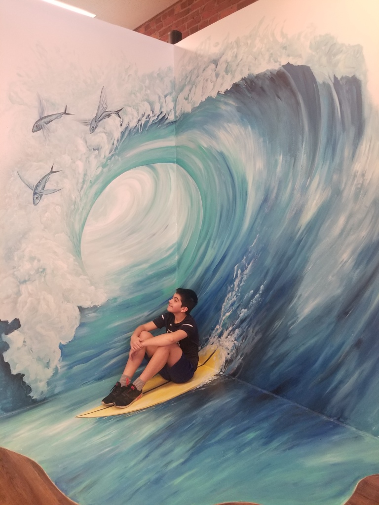 Boy sitting on surf board riding a wave - at an art installment