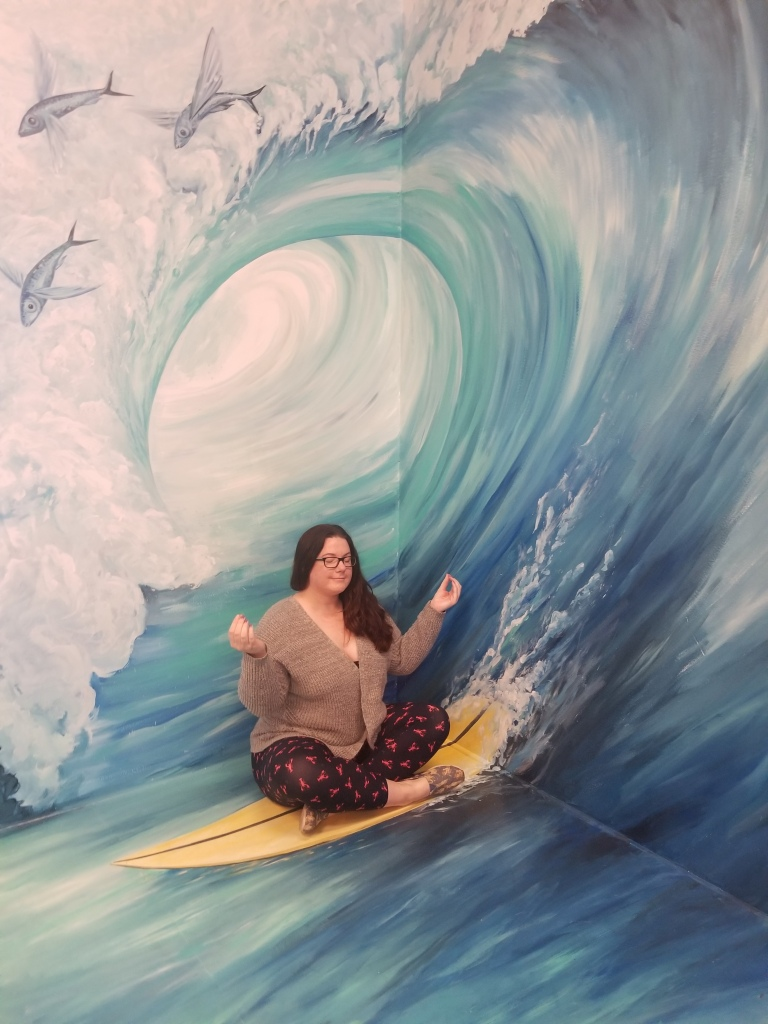 woman pretending to practice yoga while sitting on a surfboard at an art installment