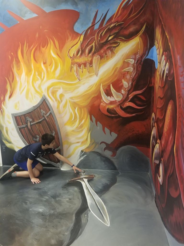 boy hiding behind shield from a fire breathing dragon at an art installment