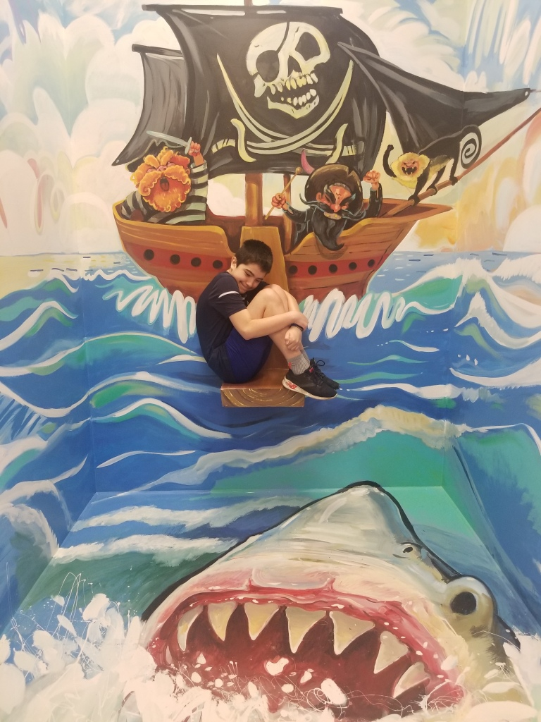 boy afraid and sitting on a plank over shark infested waters at an art installment