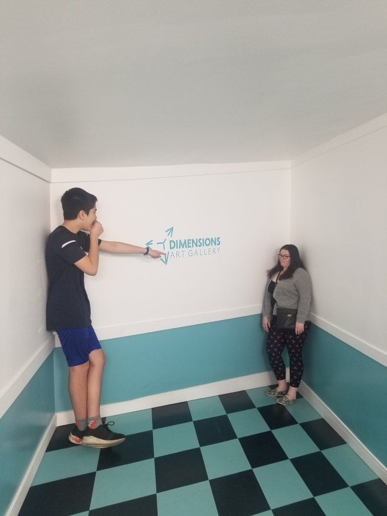 mother and son in an optical illusion room at an art installment